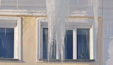 Large icicles on a house roof.