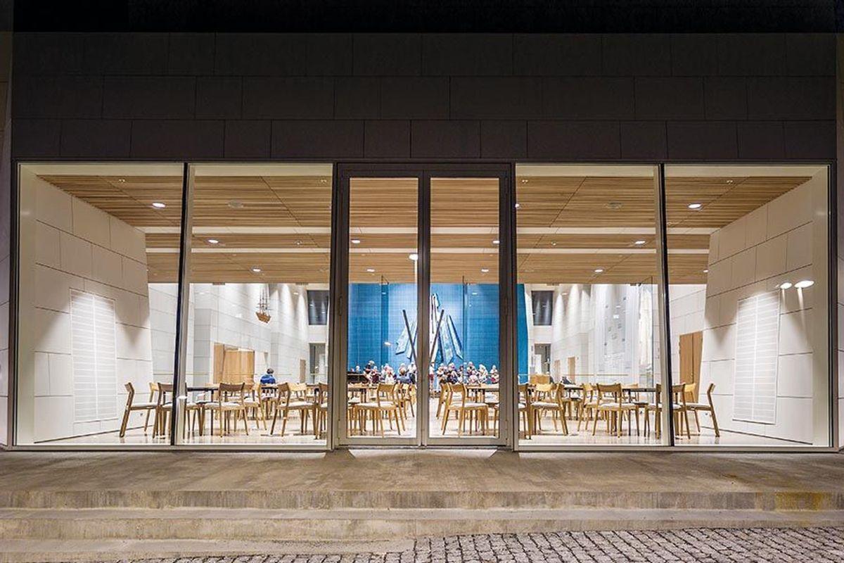 Stor glasspartier leder lyset inn i kirkestua og videre inn i kirkerommet. Foto: Michel Vo