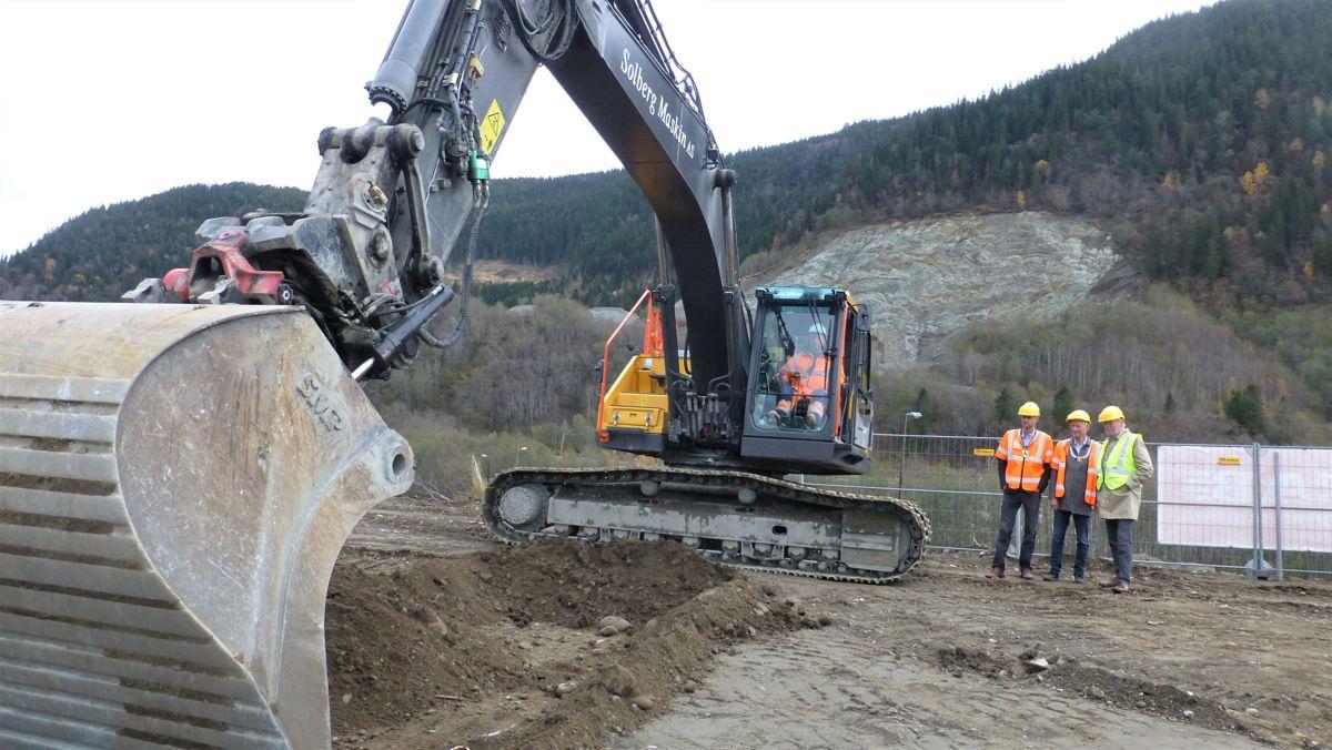 Første løft med gravemaskinen er tatt for 700-milllioners prosjektet for Nye Veier i Melhus med tre ordførere som ivrige tilskuere, og maskinfører Geir-Olav Stein fra Solberg Maksin ved spakene.