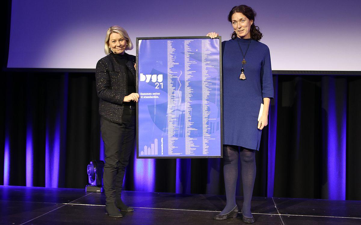 Kommunal- og moderniseringsminister Monica Mæland fikk overrakt et stort minne om arbeidet i form av en plakat med alle som har signert Bygg21-signaturen av styreleder Sissel Leire i Bygg21.
