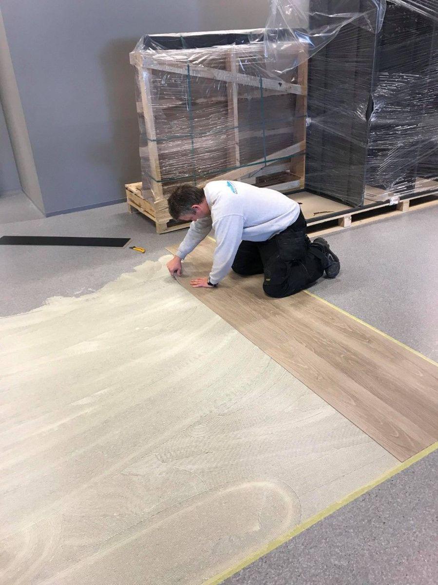 Jon Erik Holme i Malermestrene Edvin & Eilert Holme AS legger gulv på et byggeprosjekt i Sogndal