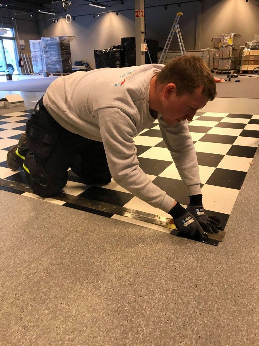 Eilert Holme i Malermestrene Edvin & Eilert Holme AS legger gulv på et byggeprosjekt i Sogndal