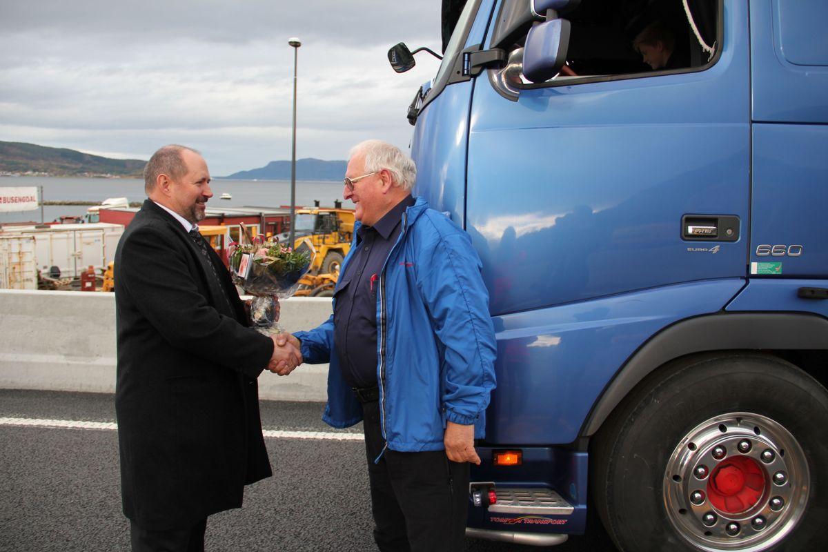 Styreleder i Eksportvegen Roald Fiksdal (til venstre) gir blomster til første betalende bilist over brua. Foto: Statens vegvesen