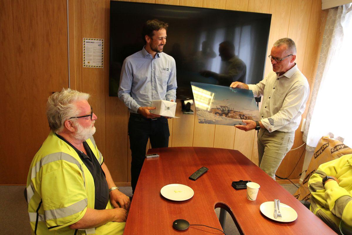 Administrerende direktør Erik Sollerud og storkundeansvarlig Pål Brandvold i Pon Equipment, hadde med gave til jubilanten Kåre Johnsen.