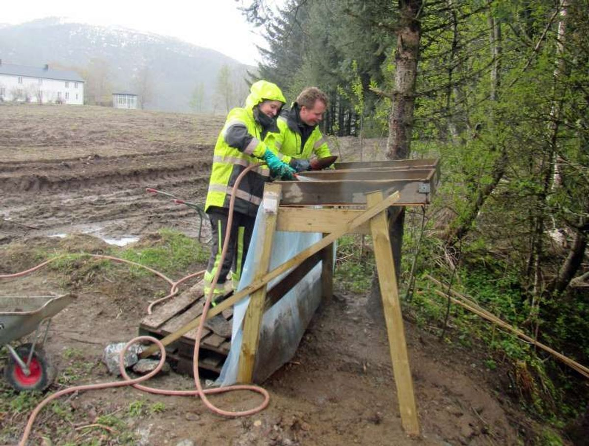 Arkeologer ved NTNU Vitenskapsmuseet vasker gjennom jorda i jakten på spor fra fortiden. Såldestasjonen er på feltet Skeiet, som ligger ved Vinjeøra. Foto: Johanne Ranvik, Statens vegvesen