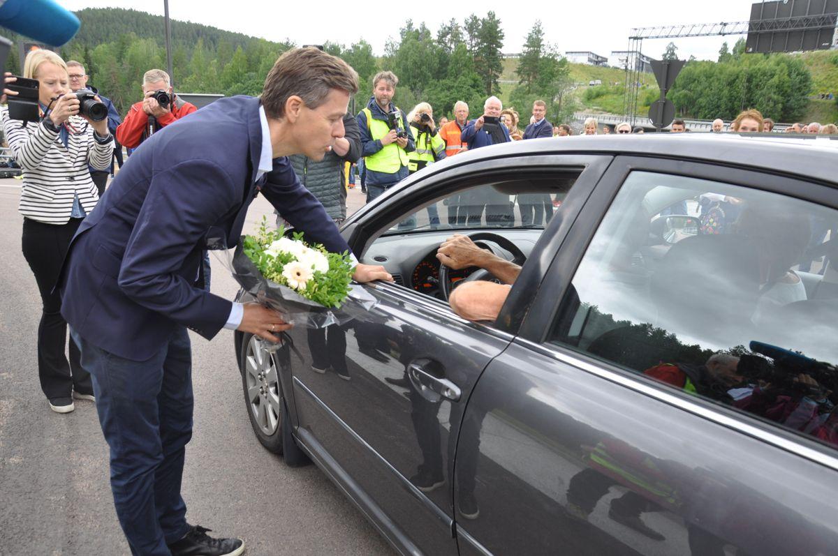 Statsråden med blomst til første bilist. Foto: Kjell Wold/Statens vegvesen