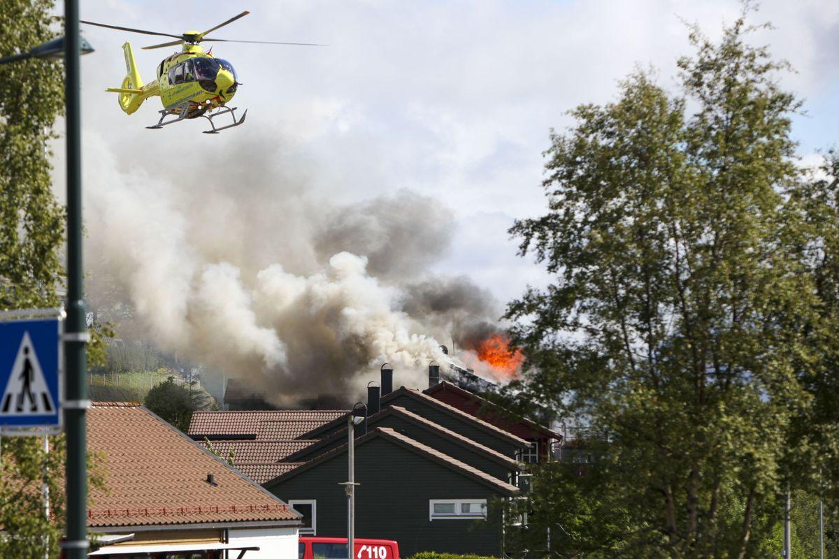 Et ambulansehelikopter i lufta over stedet der det brenner i flere rekkehusleiligheter i Florø. Foto: Egil Aardal / NTB scanpix