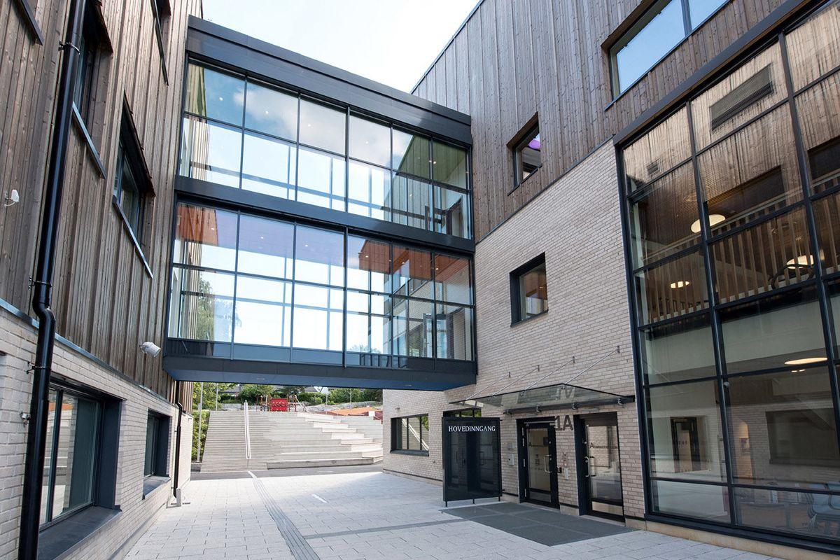 En gangbru i glass over to etasjer binder sammen hovedbygg og mellombygg, samt åpner opp bygningsmassen mot vest.