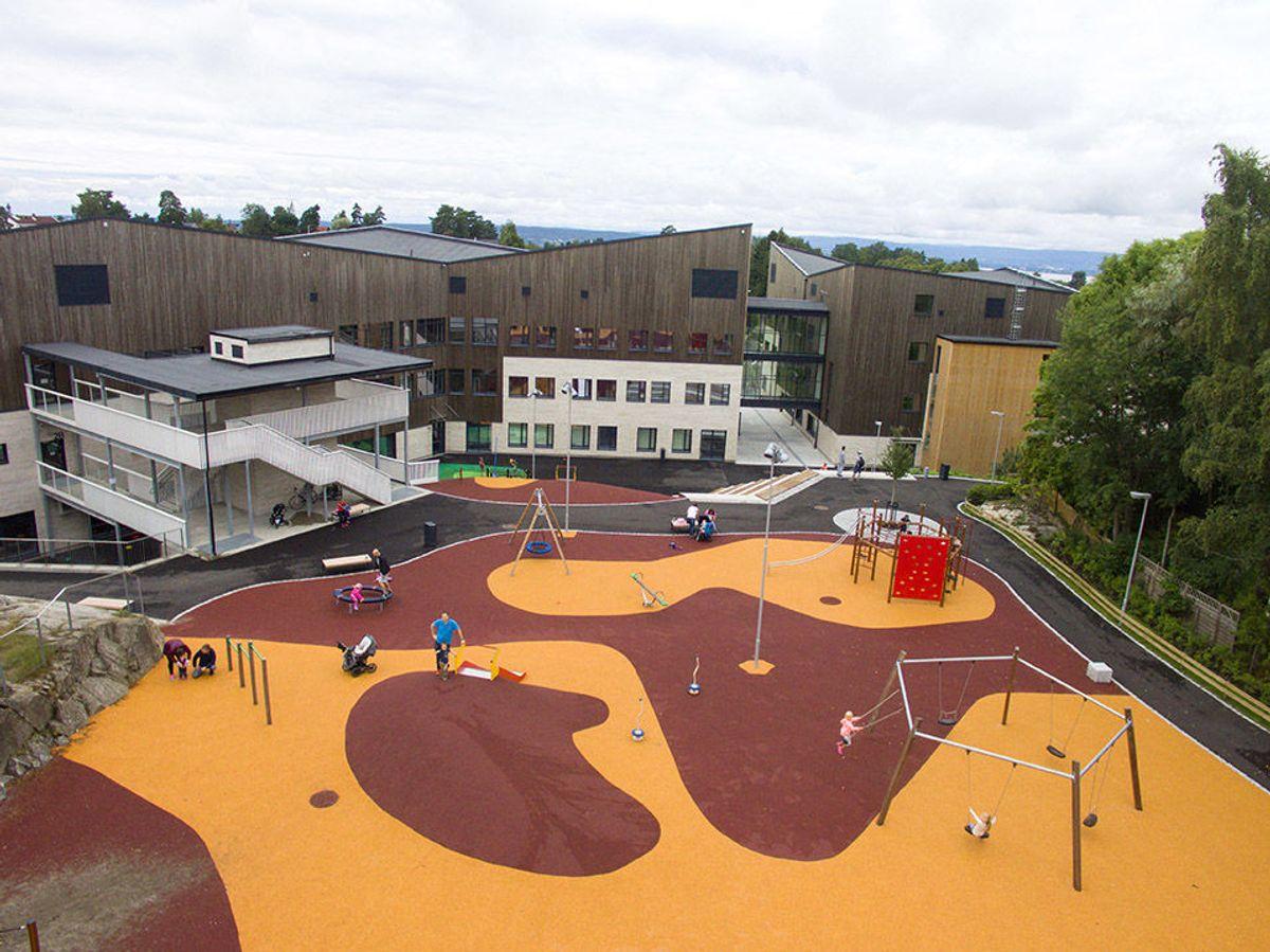 Et påkostet uteområde i entusiastisk bruk en søndag formiddag. Skolens spesielle bølgende takform ses med byen i bakgrunnen.