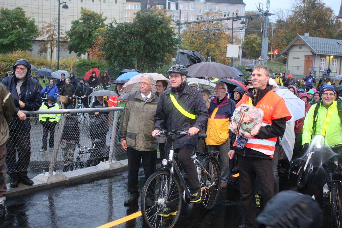 Vegdirektør Terje Moe Gustavsen til venstre venter spent på at brua skal lukke seg. Slik at den kan åpne... Erik Jørgen Jølsgard fikk æren av å være første syklist.