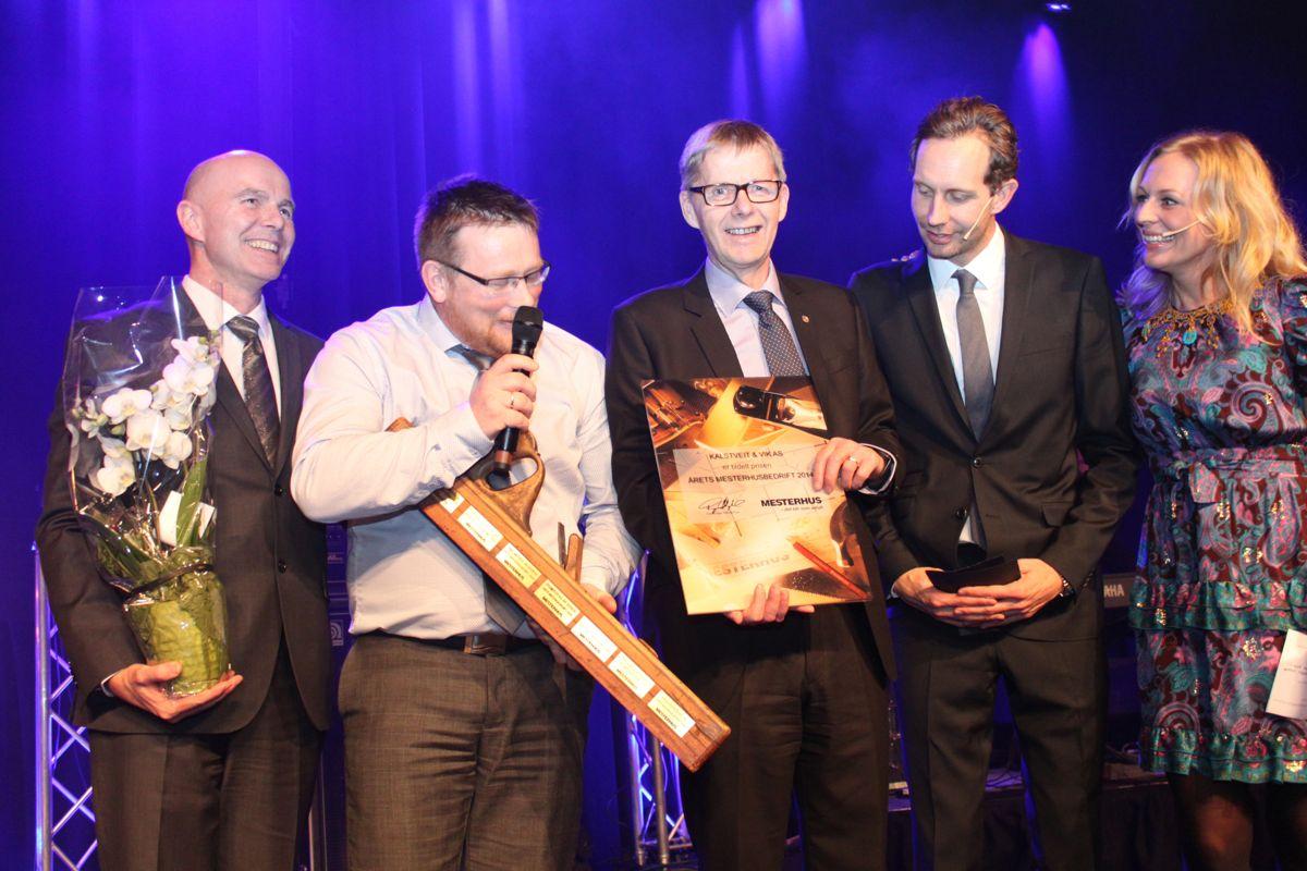 Byggmester Kjell Oddvar Vik og daglig leder Bjørn Frode Hustoft tar i mot prisen Årets mesterhusmedlem som ble delt ut av kjedeleder Raymond Myrland (til venstre). Til høyre konferansierparet Morten Ramm og Marte Stokstad.