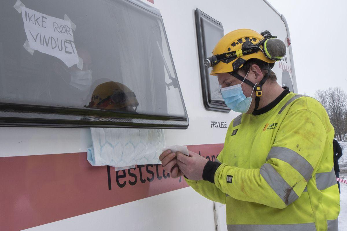 Gjennom et vindu identifiserer alle arbeiderne seg før de mottar en lapp som gis til testpersonellet på andre siden av bussen.
