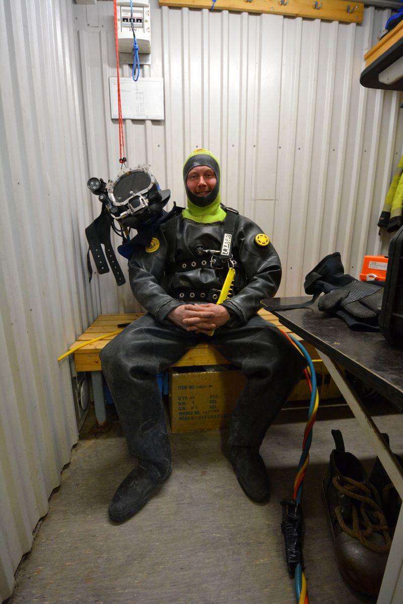 Anleggsdykker Robert Riseberg sitter i beredskap med dykkerutstyr på. Han er klar for å hjelpe dykkeren i vannet når som helst hvis han trenger hjelp.