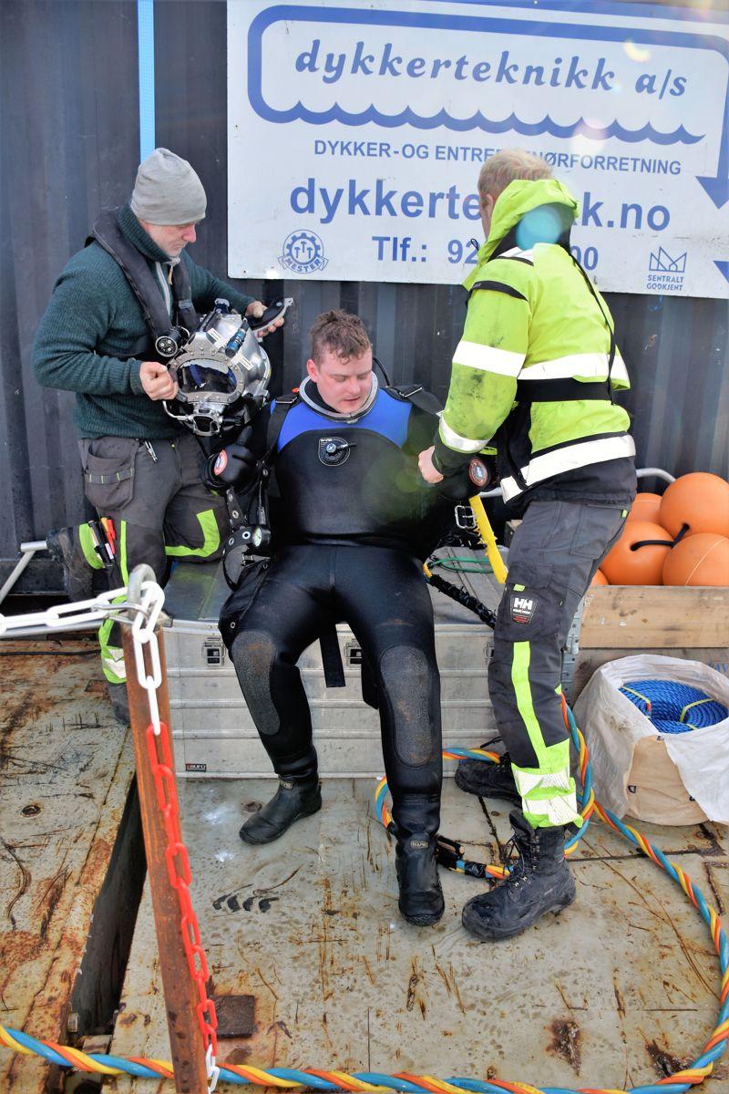 Anleggsdykkeren får hjelp til å få av seg det tunge utstyret så fort som mulig.