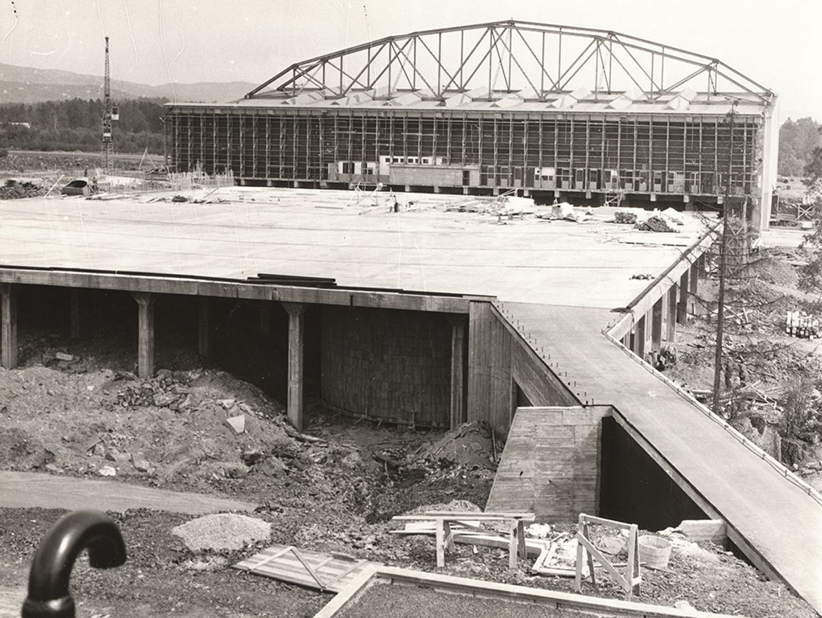 KOKSA UNDER BYGGING: Dette bildet, tatt i 1959 eller 1960, viser Hangar 1 som en frittstående struktur, med den opprinnelige bærende konstruksjonen. Arbeidene med å bygge verkstedbygget og Hangar 2 er så vidt påbegynt. Det som imidlertid allerede er bygget er plattformen foran hangar 2.  Foto: Luftfartsverket
