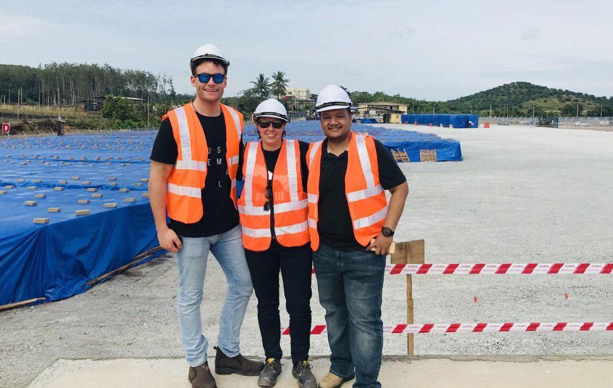 Logistikksjef Aleksander Skaare i Scatec Solar sammen med to kolleger på site i Malaysia. I bakgrunnen ligger solcellepaneler som er klare til montering.