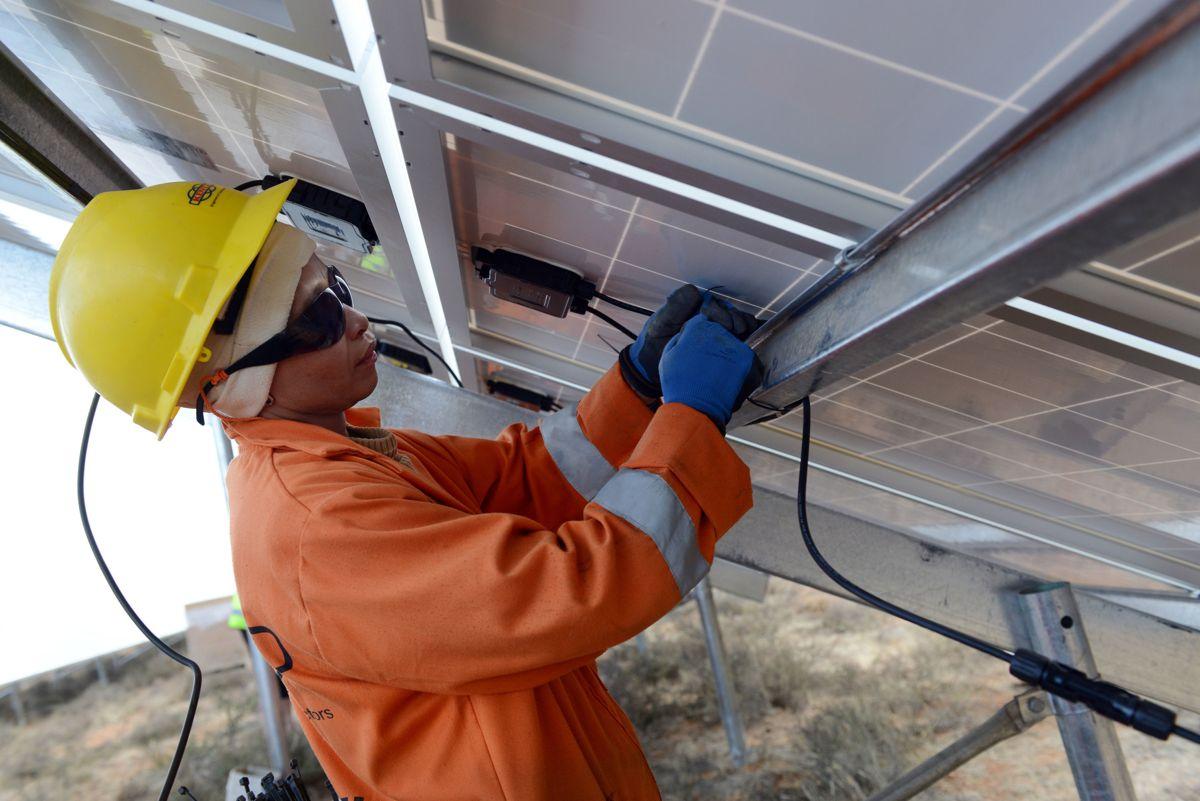 Fra montering av solcellepaneler på et av Scatec Solars anlegg i Sør-Afrika. Foto: Eric Miller