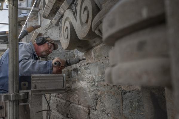Murer og steinhugger Chris Pennock meisler løs over den rikt utsmykkede Kongeinngangen på Nidarosdomen. Til neste år skal de nyrestaurerte dørene åpne igjen.