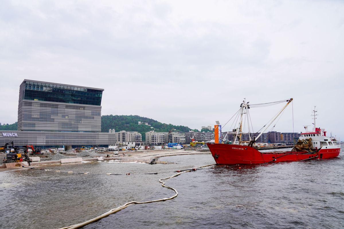 Sand fraktes med båt og spyles ut på Operastranda som ligger ved Operaen og Munch-museet i Oslo. Foto: Terje Bendiksby / NTB