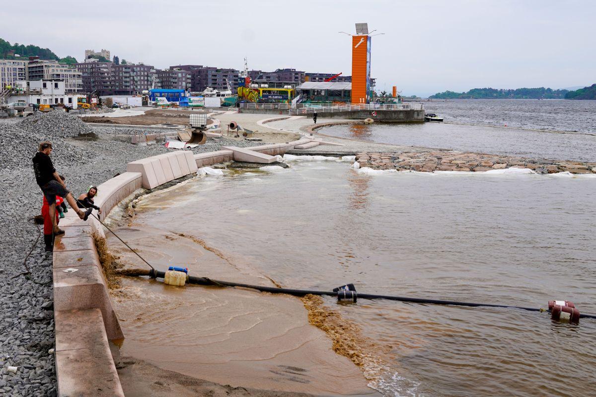 Sanden som mandag ble sprøytet ut over området, og som skal legge seg mykt rundt tærne til de badende, blir hentet i Svelvik der den har ligget siden forrige istid. Foto: Terje Bendiksby / NTB