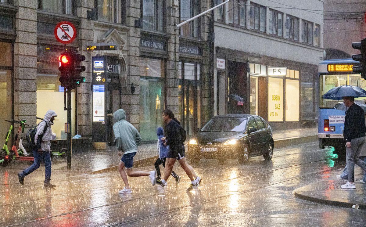 Folk løper for å søke ly fra regnet i Oslo sentrum tirsdag. Uværet vil trolig fortsette utover helgen. Foto: Geir Olsen / NTB