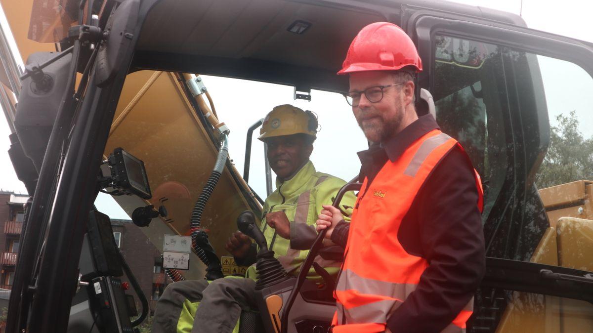 Maskinkjører Simon Y Ghebre på sin arbeidsplass demonstrerer gjerne den elektriske gravemaskinen for arbeids- og kommunalminister Torbjørn Røe Isaksen.