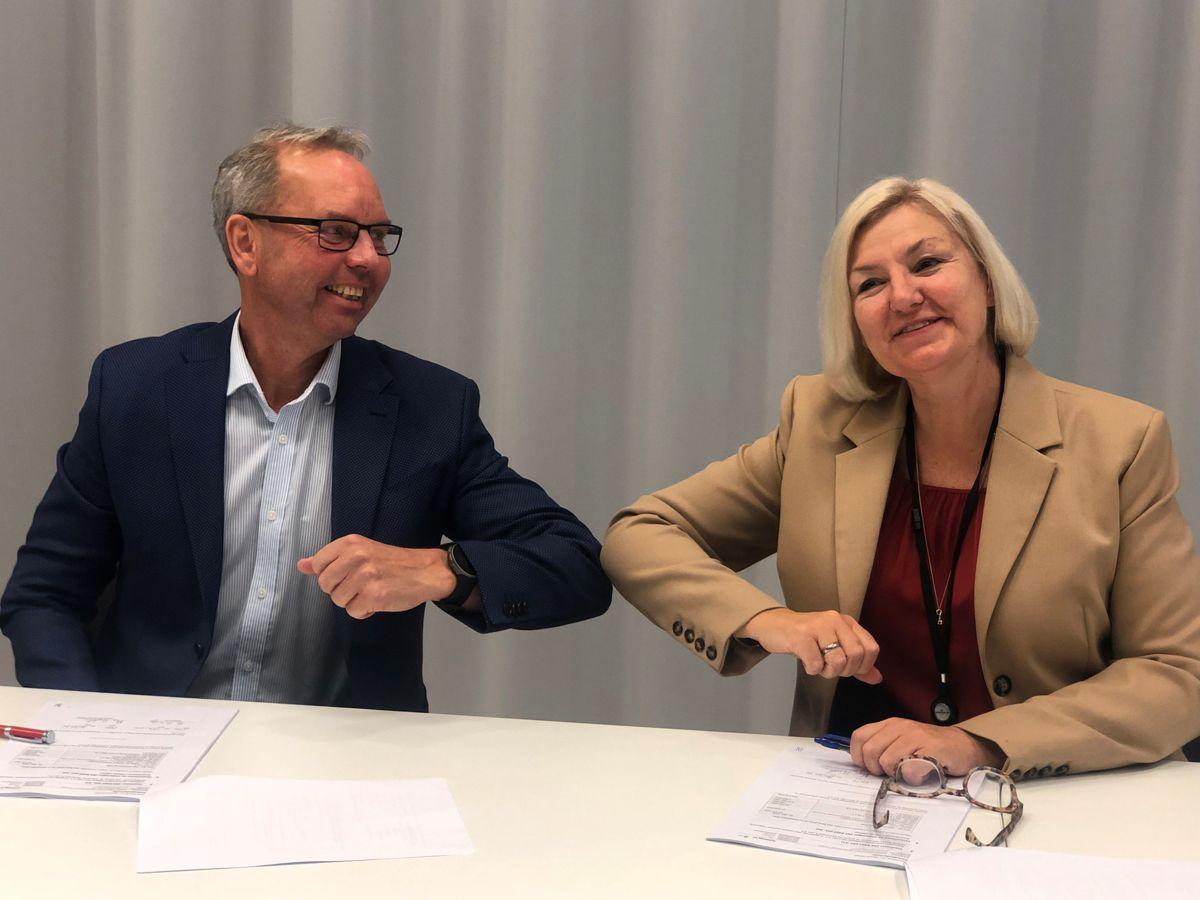 Rune Andersstuen (Veidekke) og Eli Grimsbyg (Oslobygg) signerer kontrakten for Hartvig Nissen videregående skole. Foto: Oslobygg