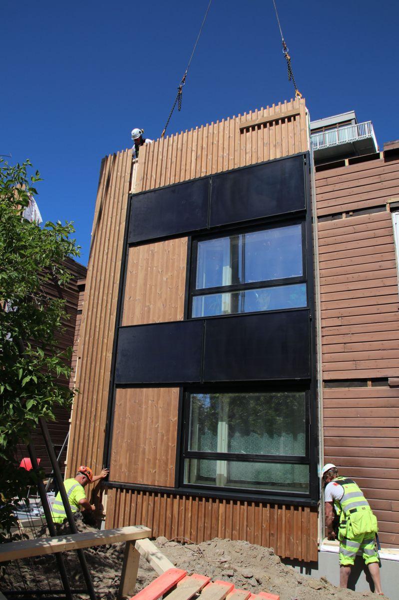 Fasadelementene heises på plass med millimeterspresisjon.