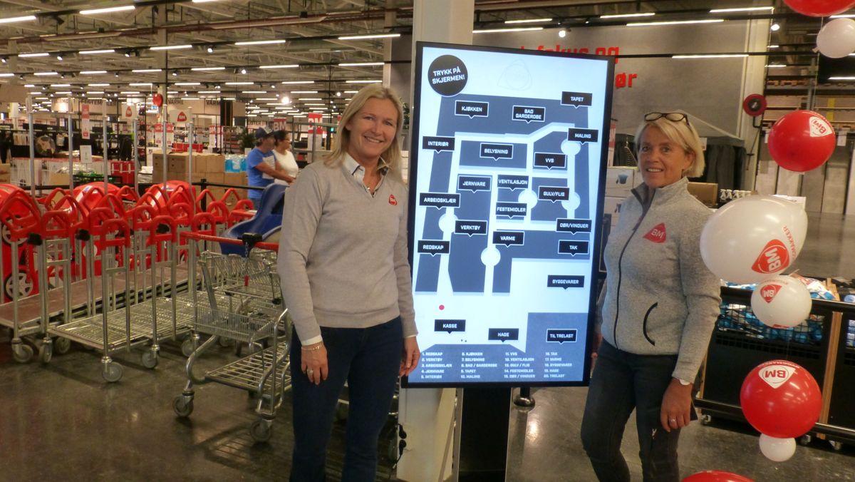 Til venstre, salg- og markedsdirektør Kari Moberg og konseptleder Anne Marthe Høgsnes ved siden av den digitale skjermen som skal vise kundene hvor varene de er ute etter finnes.