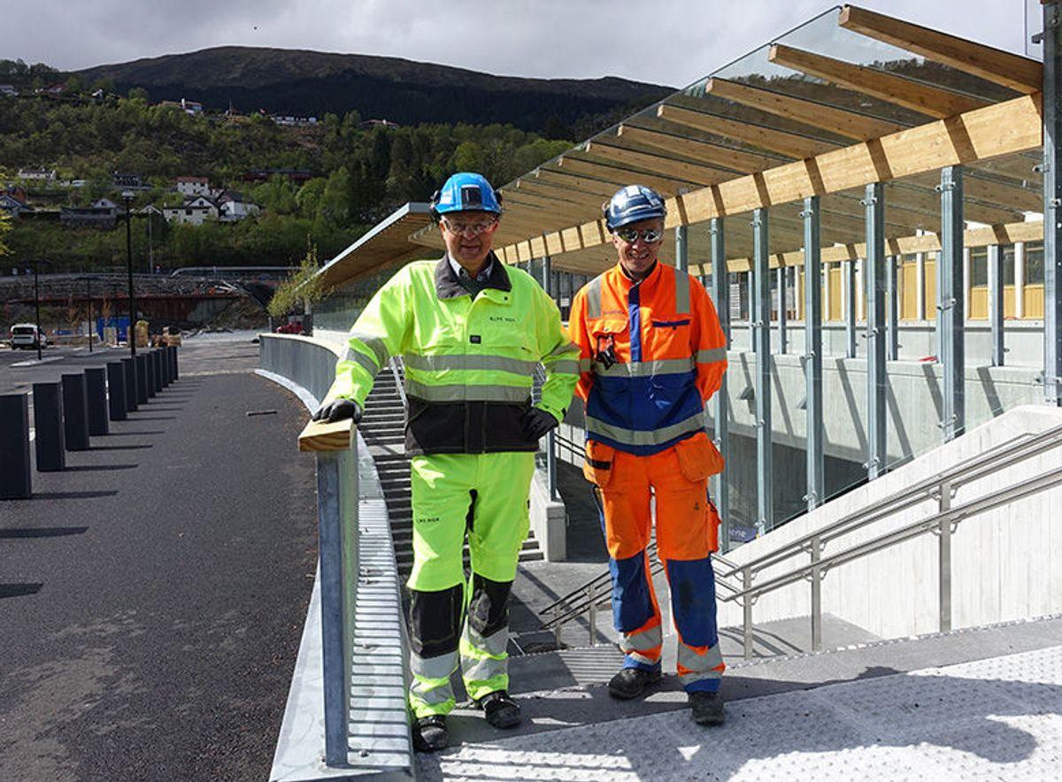 Prosjektleder Johan Kråkenes i Bane NOR (til venstre) og anleggsleder Jan Kvingedal i Skanska på toppen av trappen til den nye publikumsadkomsten på Arna stasjon. Foto: Bane Nor