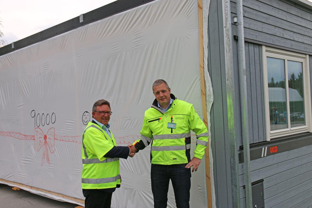 Adminstrerende direktør Jostein Stormo i UCO (t.v) og daglig leder Lars Brede Aandstad i Moelven Byggmodul, foran milepæl-modulen.
