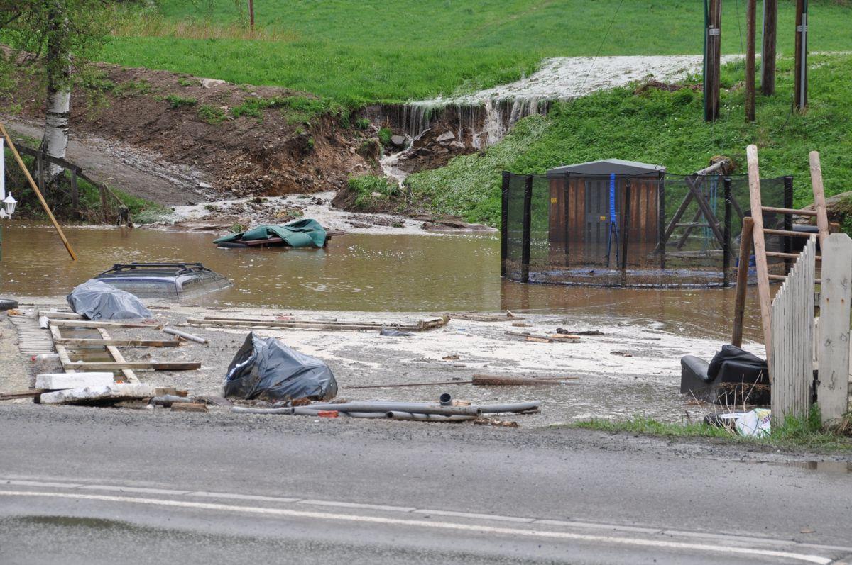 Denne eiendommen i Gata i Stange kommune ble oversvømt i løpet av kort tid. Bilen ble slukt av vannet. Foto: Heidi Kristiansen/Stange kommune
