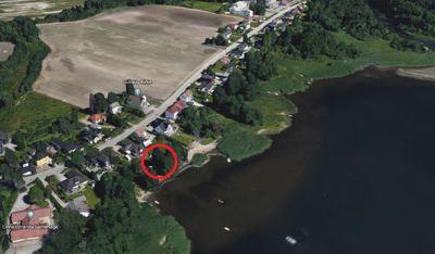 Den røde ringen viser hvor langs Linnesstranda lysthuset er oppført. Mellom boligområdet og sjøkanten er det en liten stripe naturreservat. Foto: Google Earth