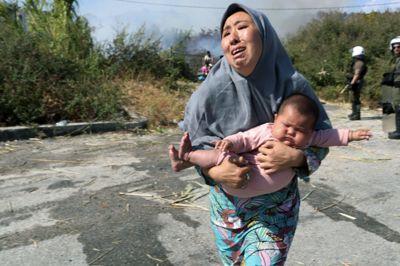 En migrant holder babyen idet hun løper for å unngå en liten brann nær Mytilene på øya Lesbos. Nå åpner Flekkefjord-ordføreren for å ta imot Moria-migranter.