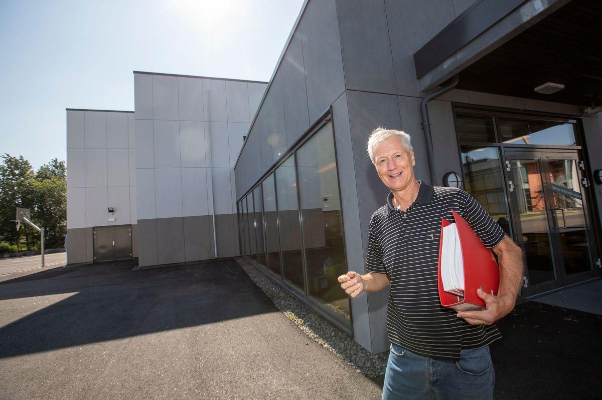 LANG HISTORIE: Den røde permen forteller deler av historien om hallens tilblivelse. Her står Tor Hansen, pådriver og nøkkelperson, utenfor nybygget. (Foto: Fredrik Naumann/Felix Features)