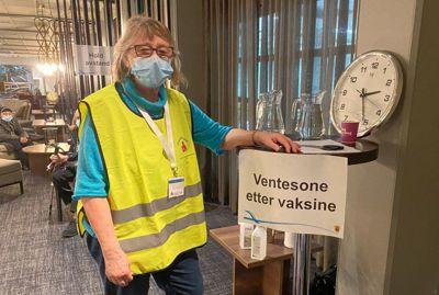 Kommunenes utgifter til kommunehelse har økt i pandemiåret 2020, viser Kostra-tall. I denne posten ligger blant annet utgifter til vaksinering. I Sarpsborg passer frivillige Aase Mjølund i Norske Kvinners Sanitetsforening i på pasientene etter at de er blitt vaksinert.