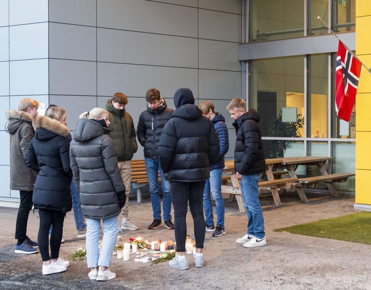 Elever står rundt om blomster og lys som er lagt ned ved Svolvær skole mandag formiddag. Foto: AIdem Media / NTB