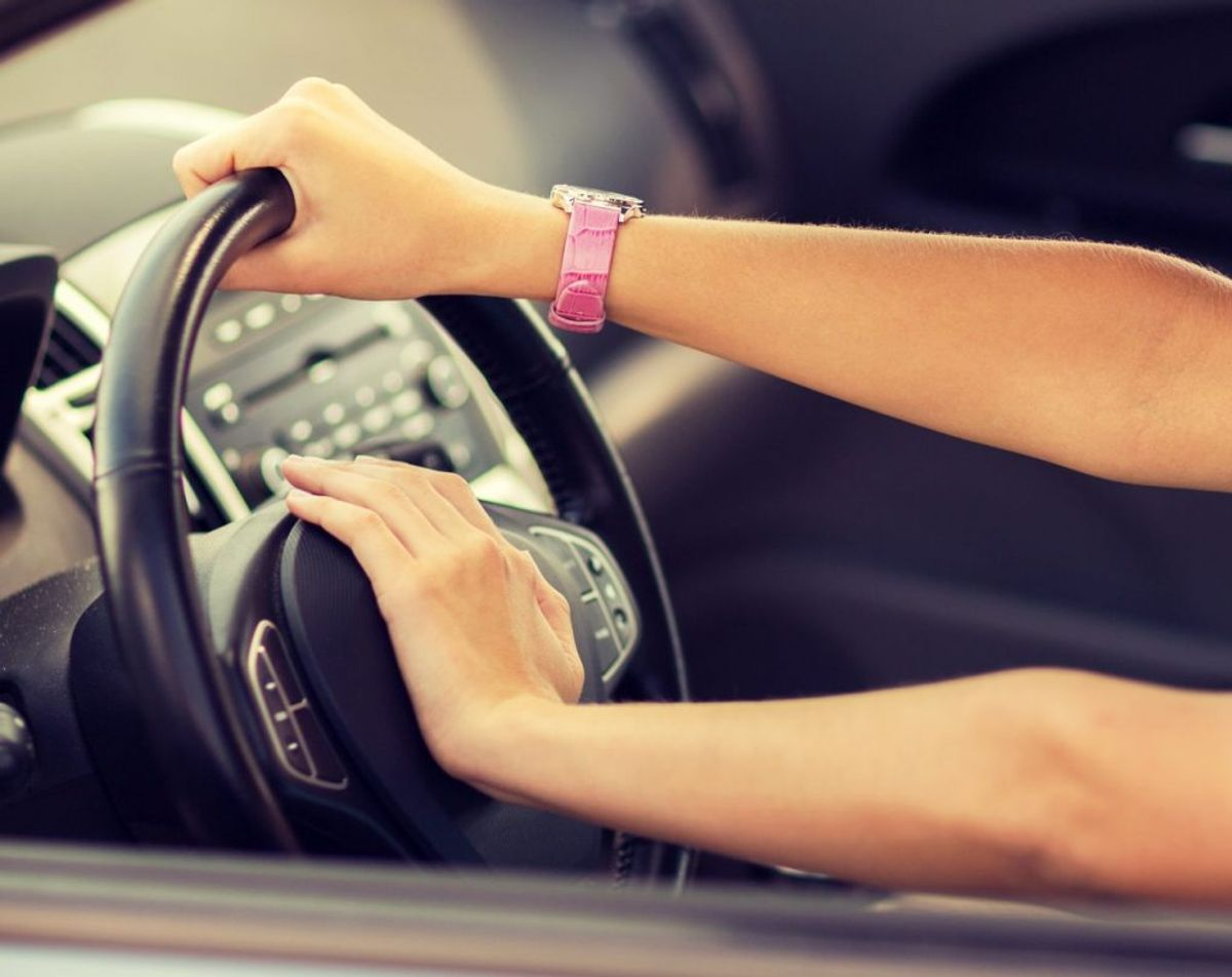 transportation and vehicle concept – woman driving a car with hand on horn button
