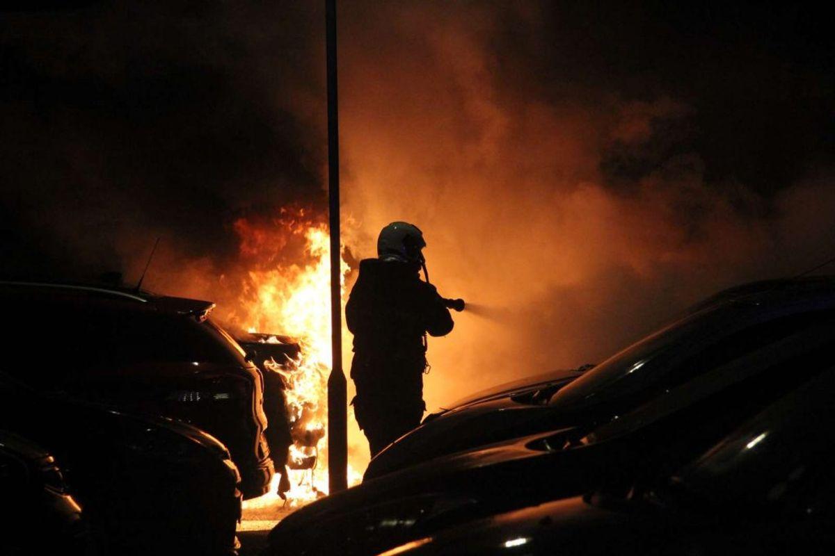 Brandmand i gang med at slukke bilbrand. Foto: Øxenholt foto/Frank Karlsen