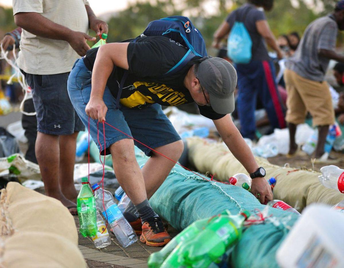Desperat forsøger indbyggere og frivillige at inddæmme olien. Foto: Scanpix