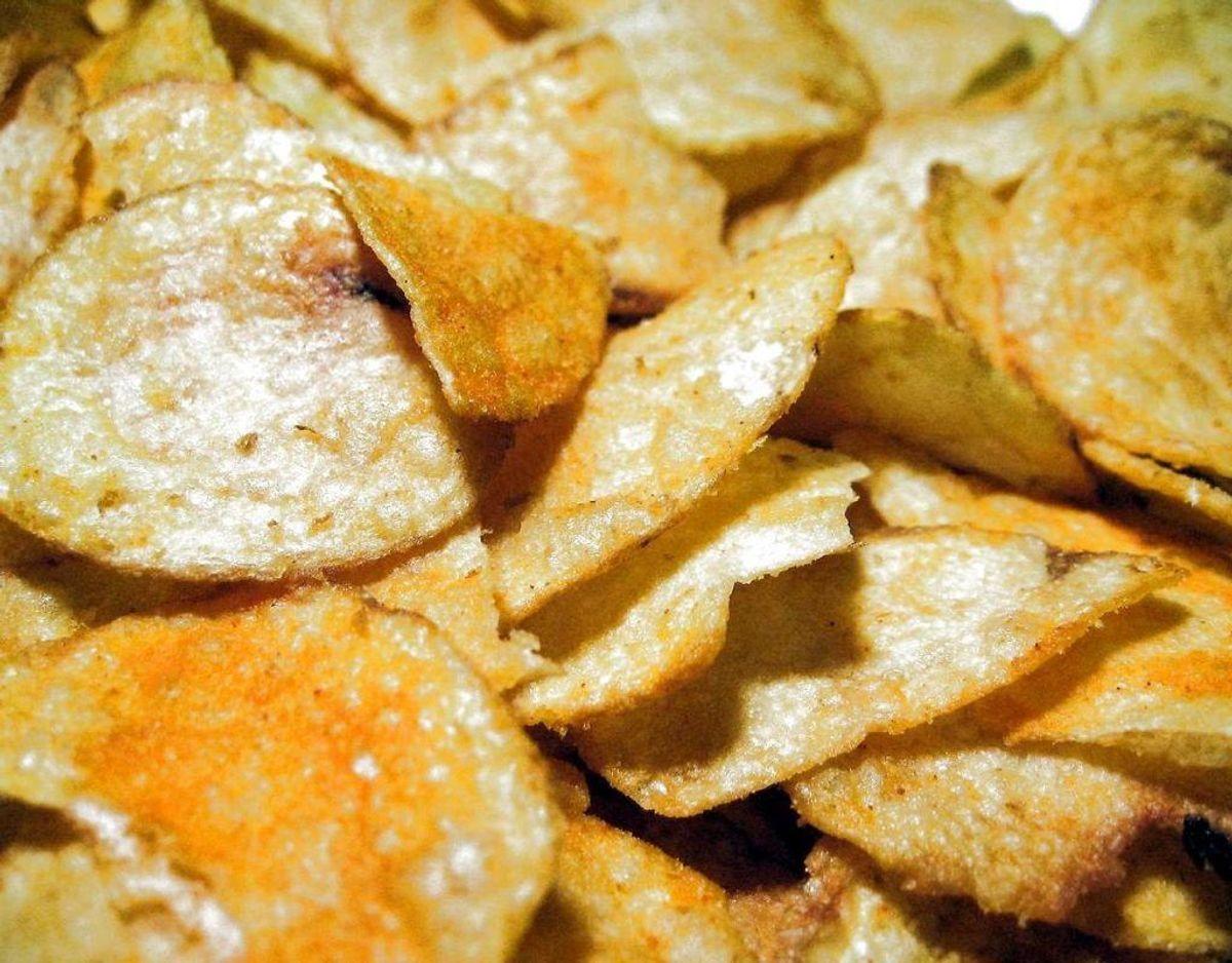 Chips, muffins og kiks fjernes bedst ved at bruge en fejebakke og en lille børste eller ved at støvsuge det op. Skulle der været fedtpletter efter eksempelvis chips, så skal du duppe det med vådt køkkenrulle og derefter putte kartoffelmel eller talkum på, som suger fedtet. Foto: Scanpix