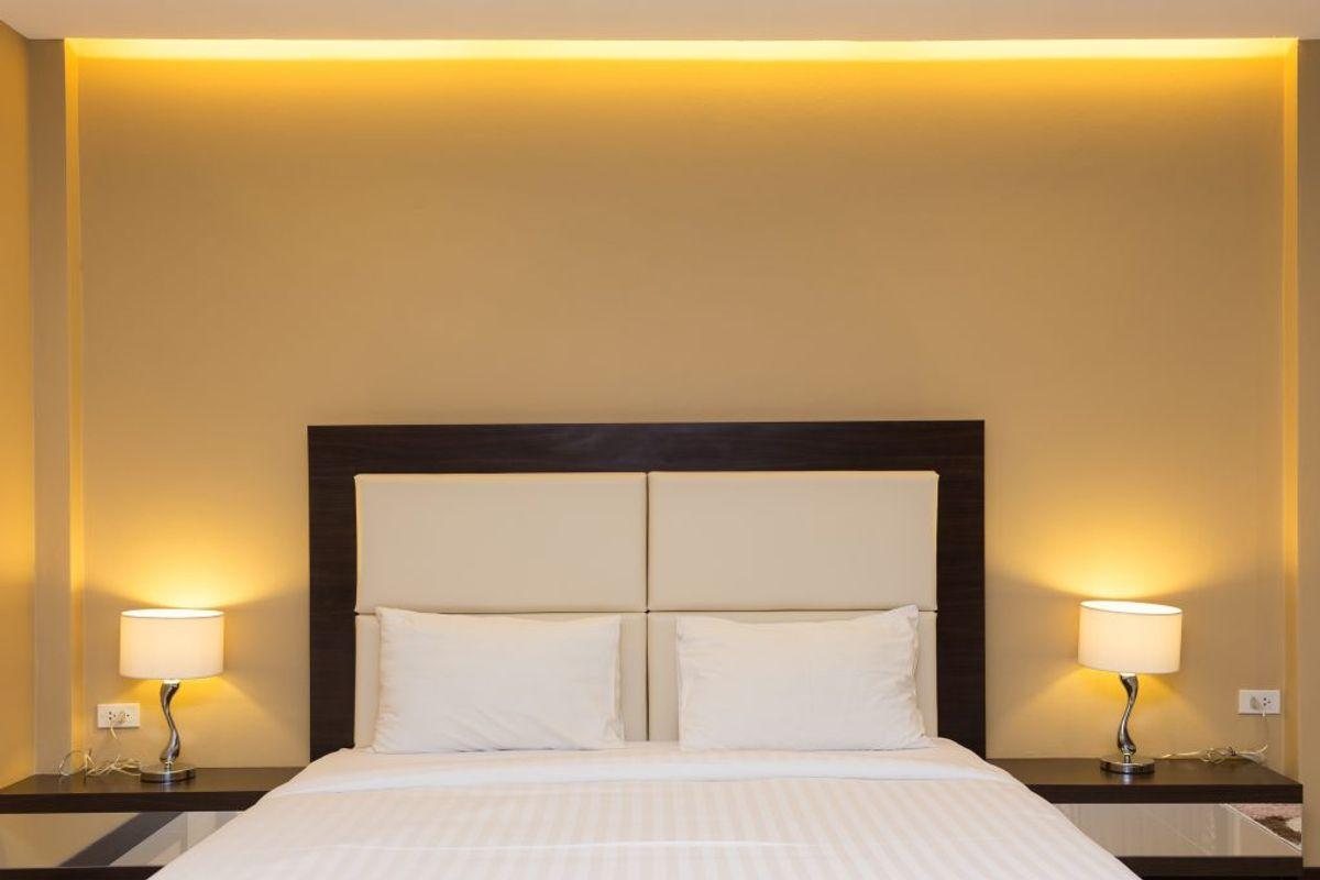 Det er lækkert at have en lampe ved sengen, men husk at støve af løbende. Foto: Colourbox
