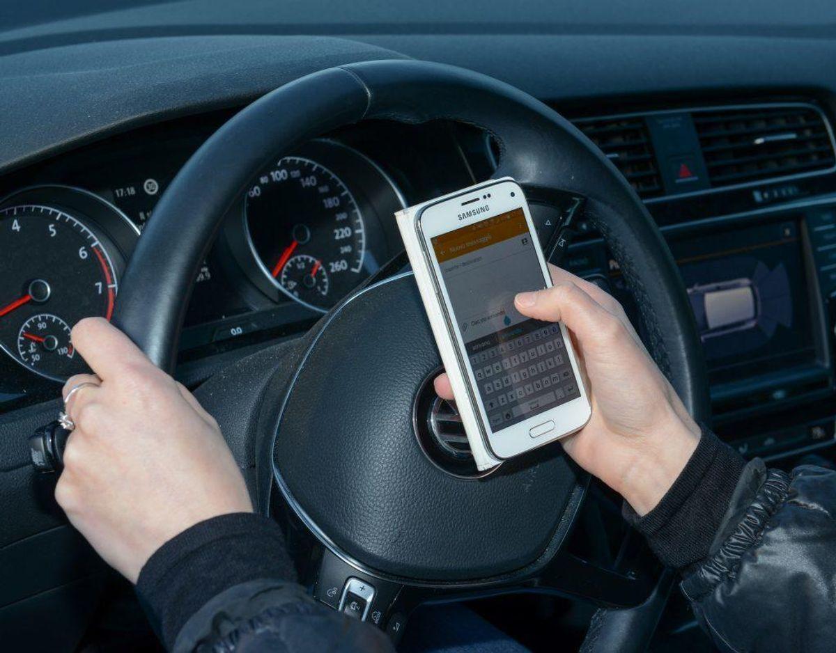 Nej. Du må ikke sms'e eller lægge ting i kalenderen mens du kører – så betjener du en håndholdt mobil og det er ulovligt. Du må heller ikke tage telefonen og sætte den på højtaler – det er stadig ulovligt.