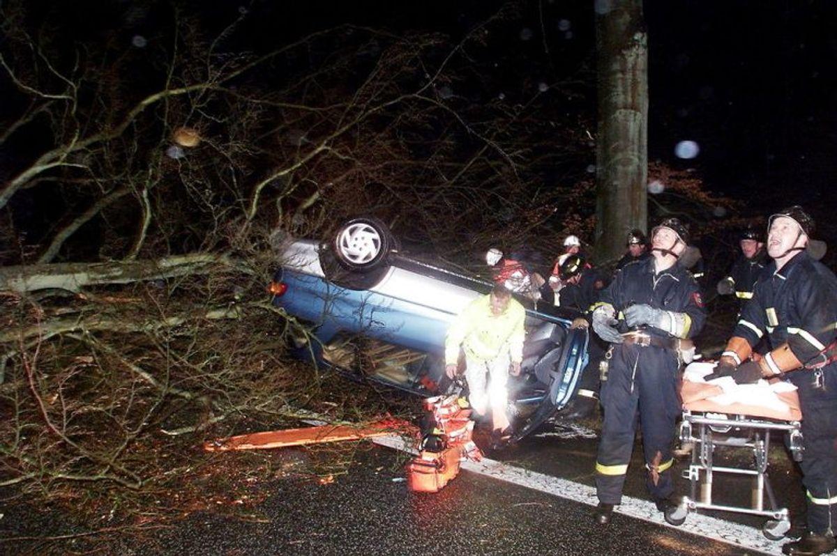 – ORKAN – Ambulancefolk holder øje med vejtrærne mens de fredag dec. 3, 1999 hjælper en bilist, som blev fastklemt, da et træ væltede hans bil.Træt til venstre faldt ned under redningsarbejdet. Ambulancen måtte køre en stor omvej for overhovedet at komme frem til ham. På vej til sygehuset i Slagelse måtte de standse fire gange for at rydde vejen for træer. Søren Steffen/NORDFOTO
