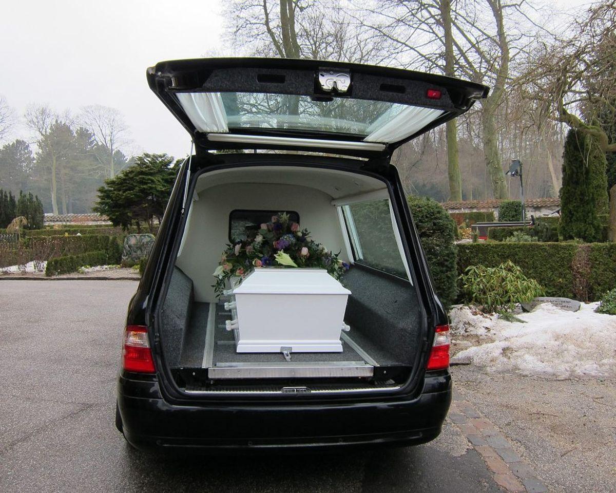 Efter en bisættelse bliver kistet båret ud til rustvognen, der siden kører væk med kurs med krematoriet. Arkivfoto: Colourbox