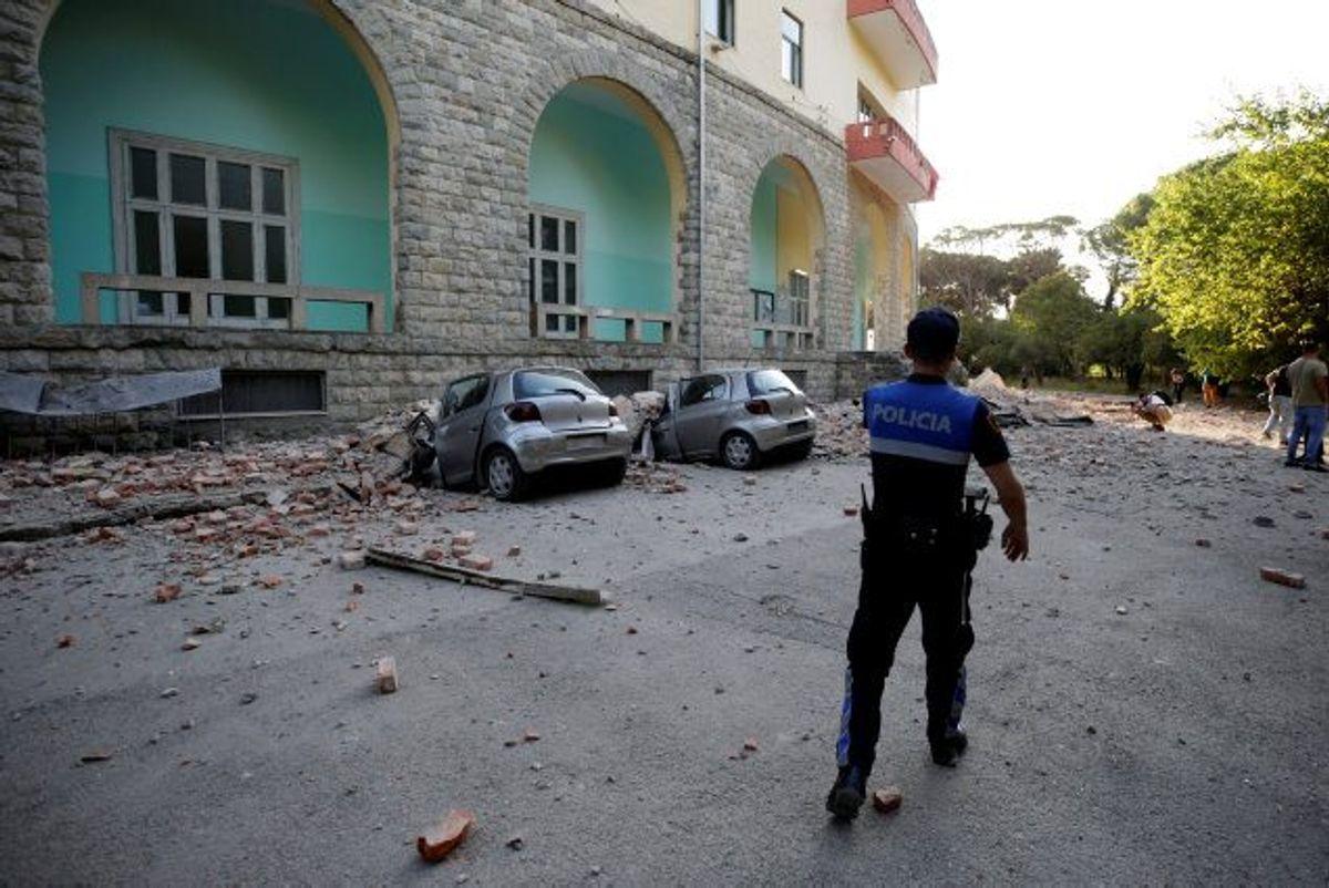 En politimand går forbi to beskadigede biler og en delvist ødelagt bygning i hovedstaden Tirana, der lørdag eftermiddag blev ramt af et jordskælv. Foto: Florion Goga/Reuters