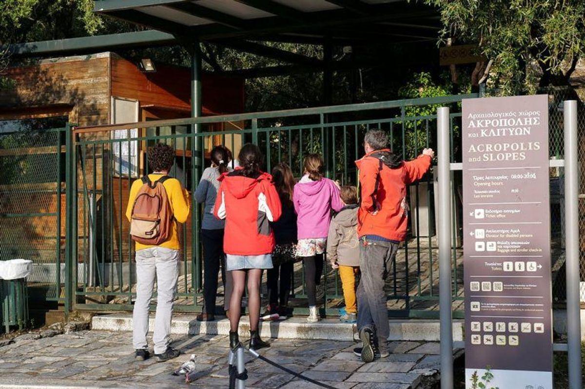 Turister mødte en lukket port ind til Partenon-templet i Athen. En kvinde og tre mænd med skadet ved et lynnedslag onsdag. Foto: Scanpix/Vassilis Triandafyllou