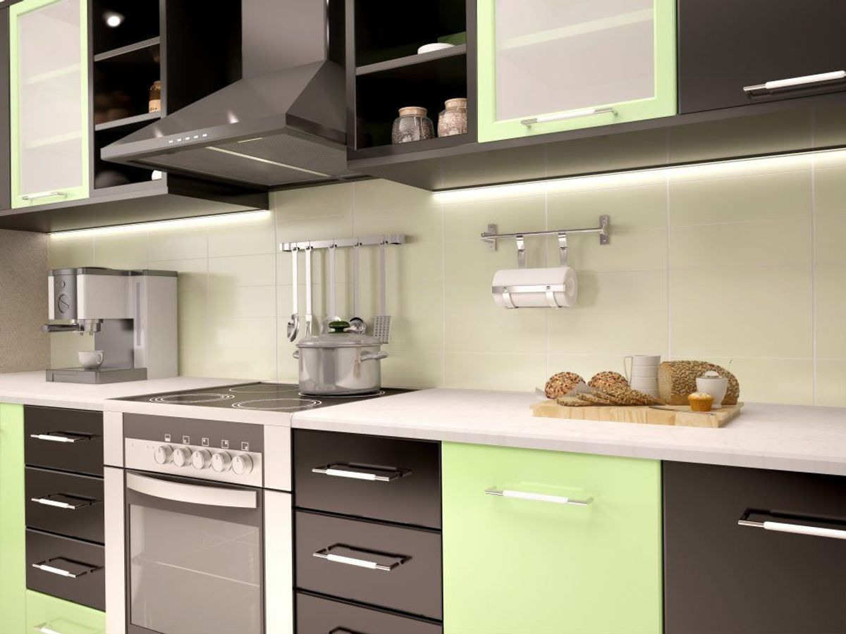 Køkkenskabenes overflader rengøres ved at spraye varmt vand blandet med opvaskemiddel på dem. Tør efter med en hårdt opvredet klud. Foto: Colourbox.