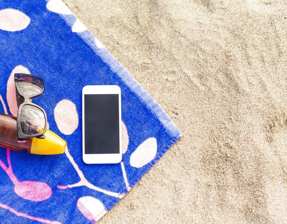 Du skal nok ikke lægge telefonen fra dig i solen.  Først og fremmest kan solen overophede batteriet, der kan bryde i brand, men varmen kan også fremme kondensudvikling, så telefonen tager fugtskade. Foto: Scanpix