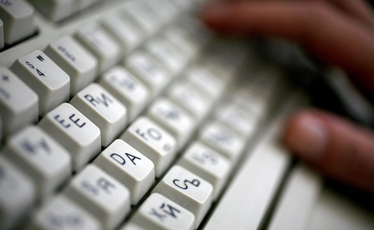 """An employee types on a computer keyboard with both Latin and Cyrillic letters in Sofia in this June 23, 2008, file photo. The regulatory body that oversees Internet domain names voted on Monday to revamp the domain naming system for websites, allowing them to end with words like """"apple"""" and """"orange"""" instead of suffixes such as """".com"""" or """".gov"""". REUTERS/Stoyan Nenov (BULGARIA – Tags: SOCIETY POLITICS SCI TECH BUSINESS)"""